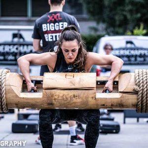 Macy Smulders tilt een boomstam tijdens Strongman